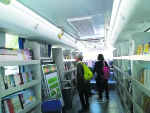 读者在流动图书车上精心挑选图书