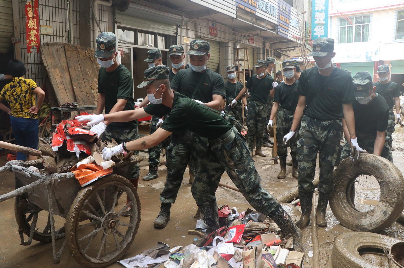 武警赣州支队官兵在江西省瑞金市九堡镇菜市场合力清理淤泥和垃圾(7月19日摄)。