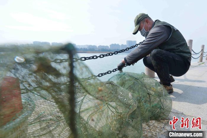 志愿者对清理的地笼网做无害化处理。 王海滨 摄