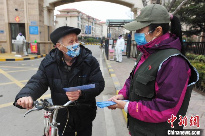 """志愿者向社区居民发送""""禁食野味""""宣传单。 王海滨 摄"""