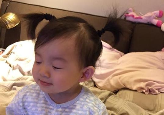 """"""" 照片上,小玥儿坐在乱糟糟的床上,眯着眼睛微微笑着,样貌上跟父母"""